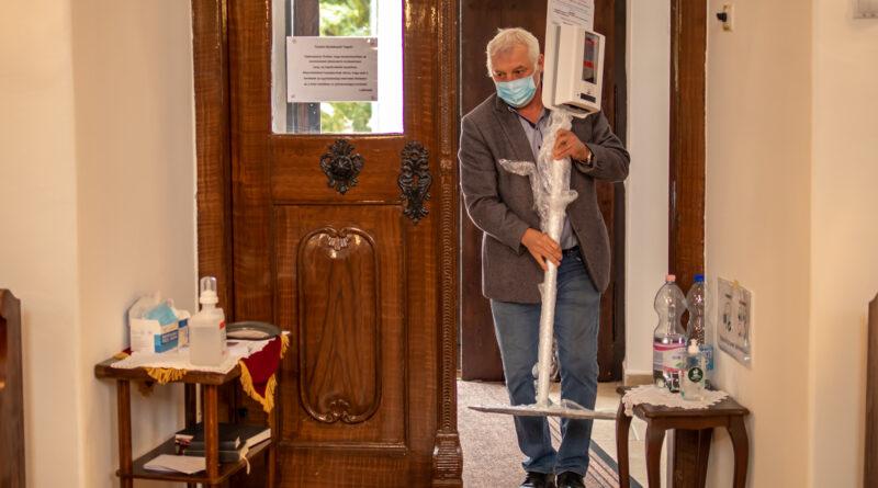 Ulbert Sándor önkormányzati képviselő, automata kézfertőtlenítőt visz a református templomba. Fotó: Szép Zsóka/TelePaks